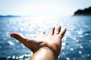 Main ouverte vers le ciel au-dessus de la mer